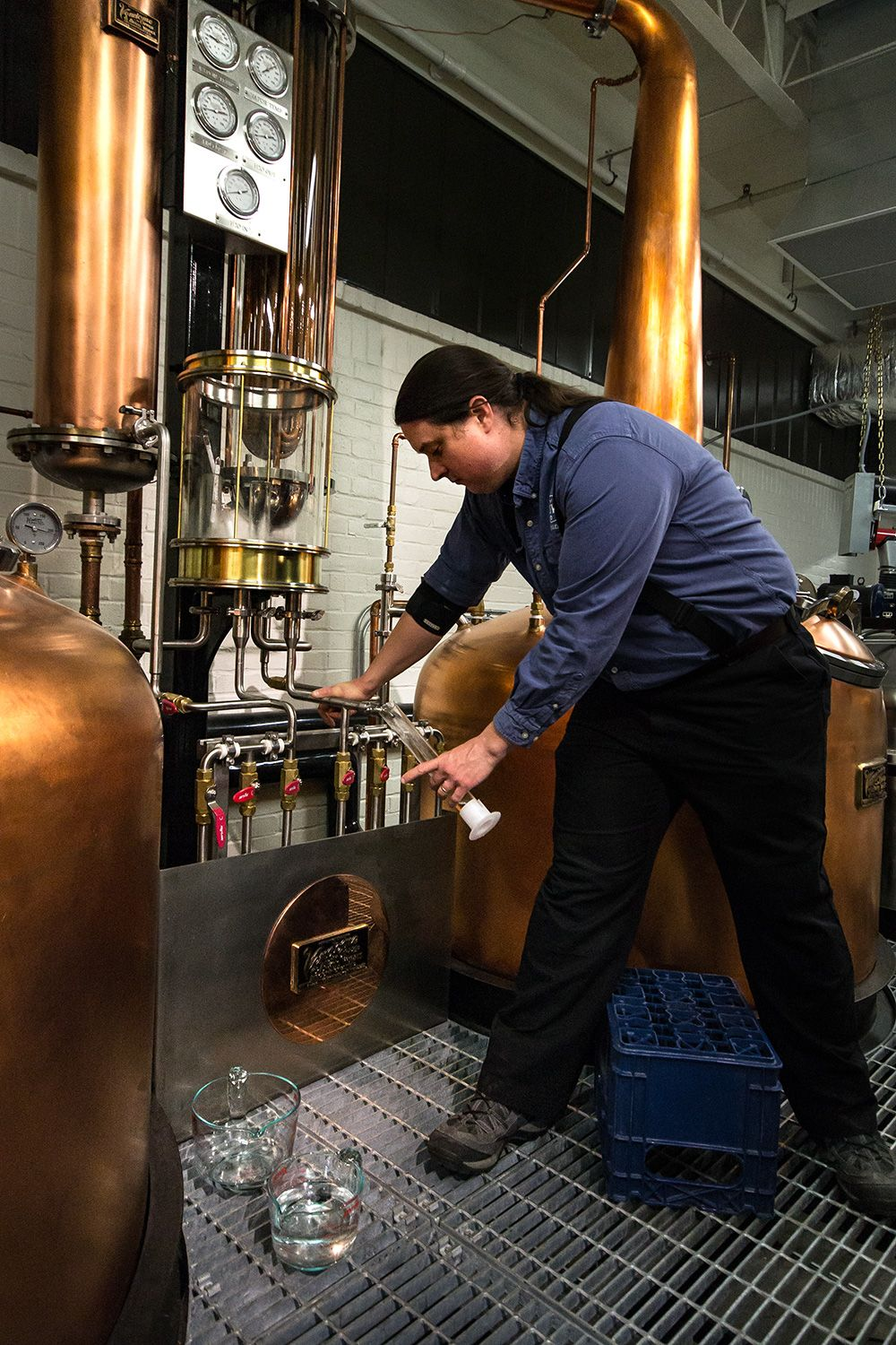 Employee Justin takes a sample during the distilling process.