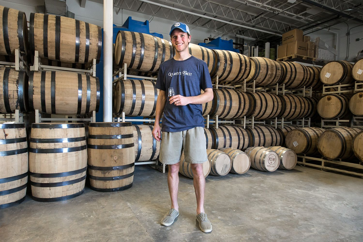 Employee Chad tasting whiskey inside the rick house.