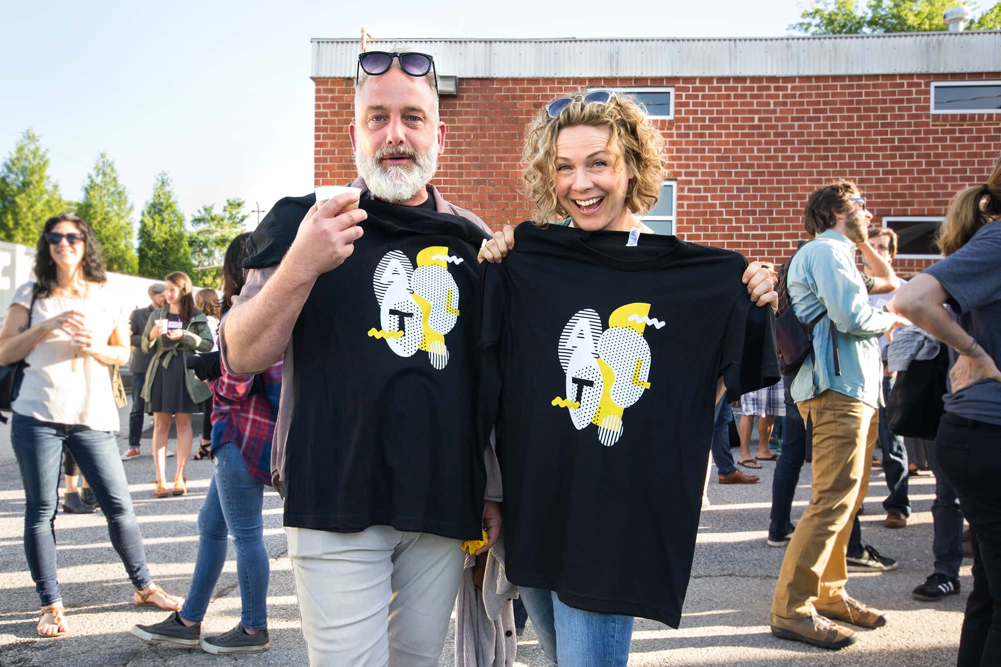 Two attendees posing while holding their event t-shirts.