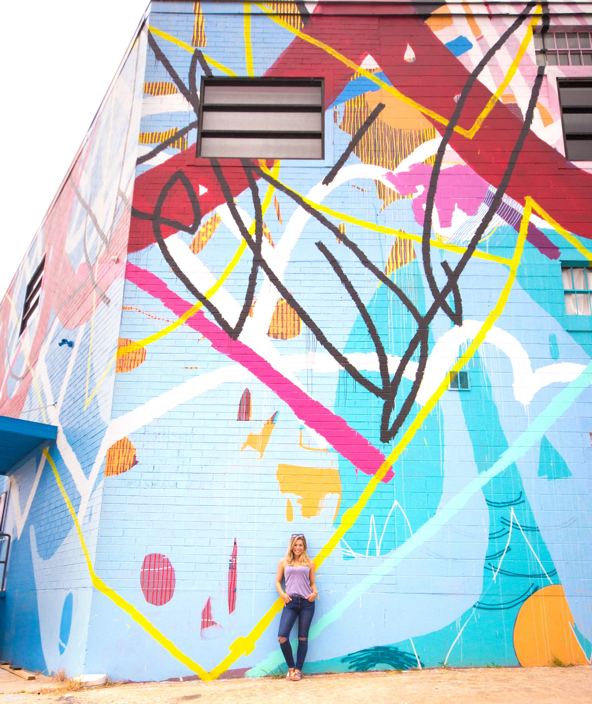 Posing in front of a large colorful mural.