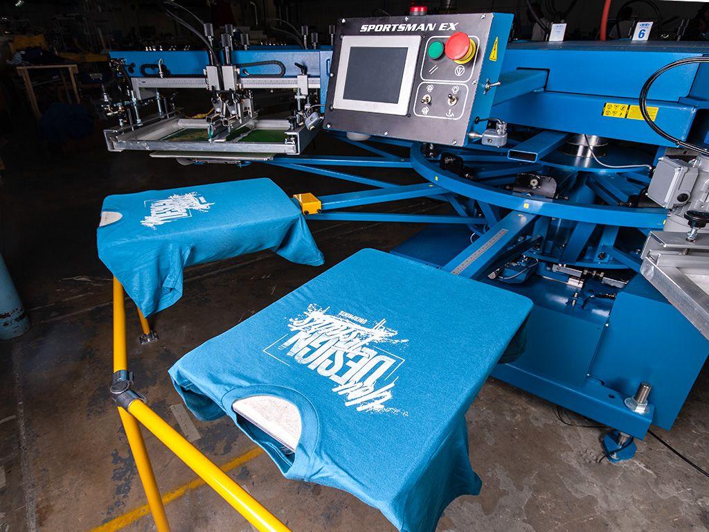 An automatic screen printing press printing an UberPrints themed t-shirt design.