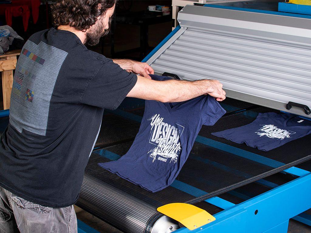 A press operator placing printed t-shirt onto a gas belt dryer.