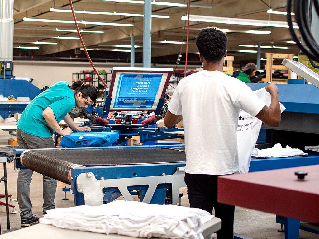 A candid shot of screen print press operators completing customer orders.