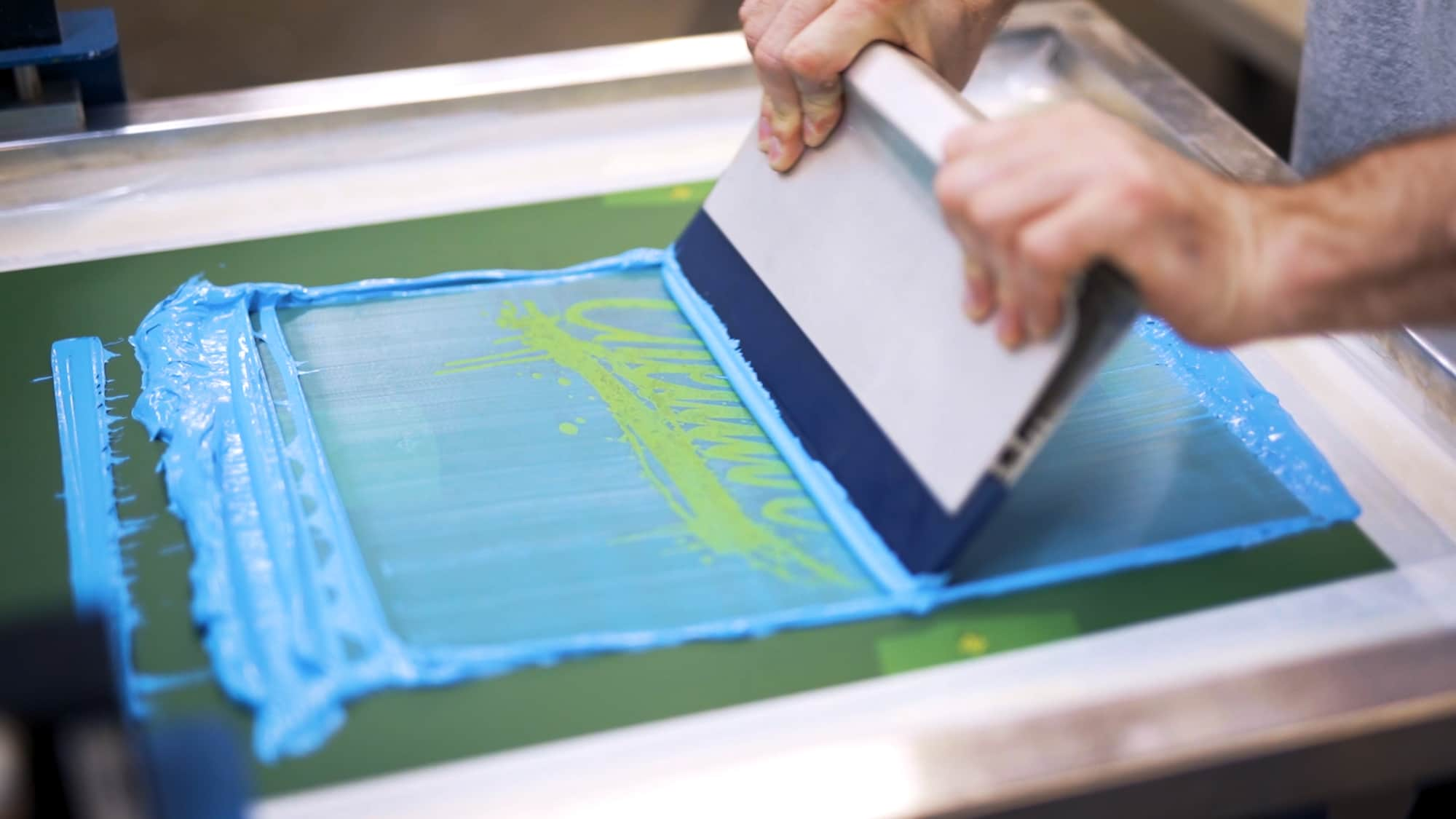Manually pushing a screen printing squeegee.