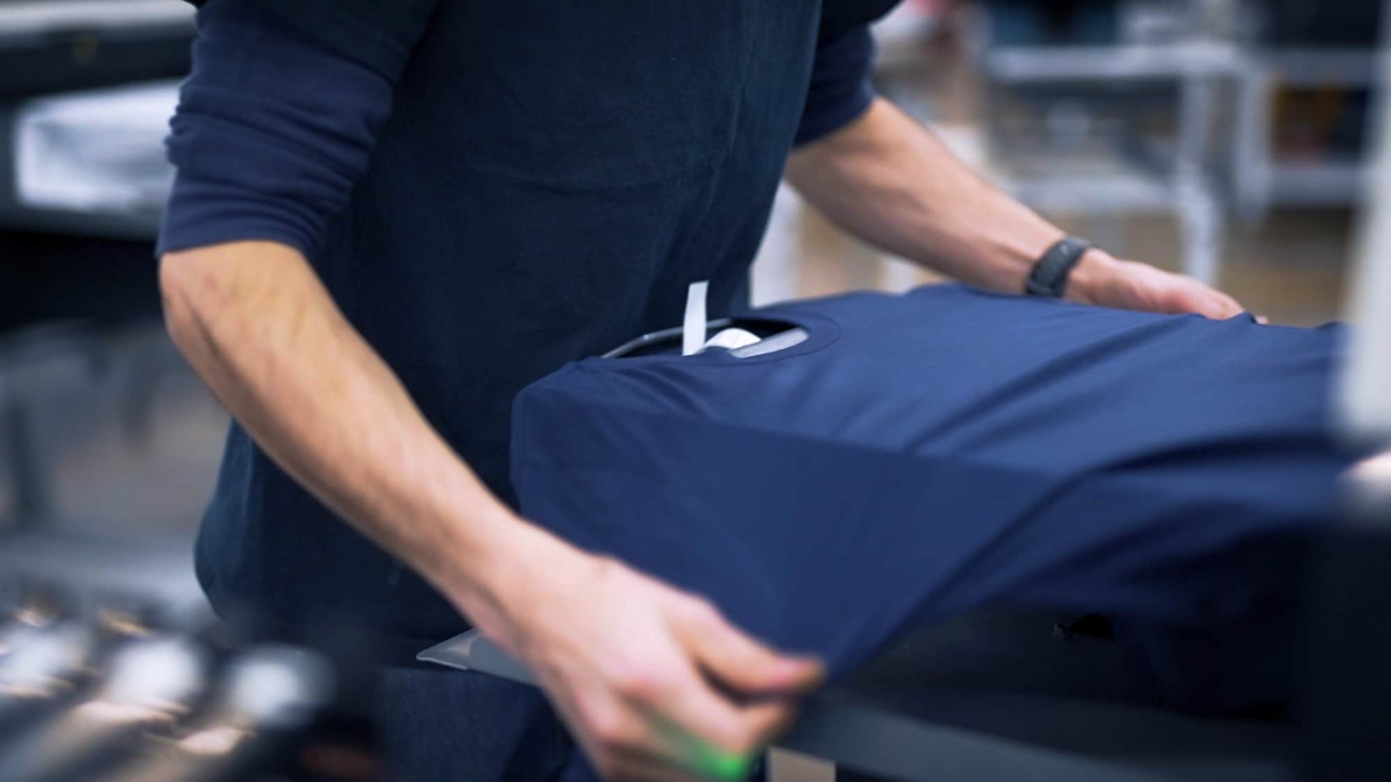 An operator loading a t-shirt to be digitally printed.
