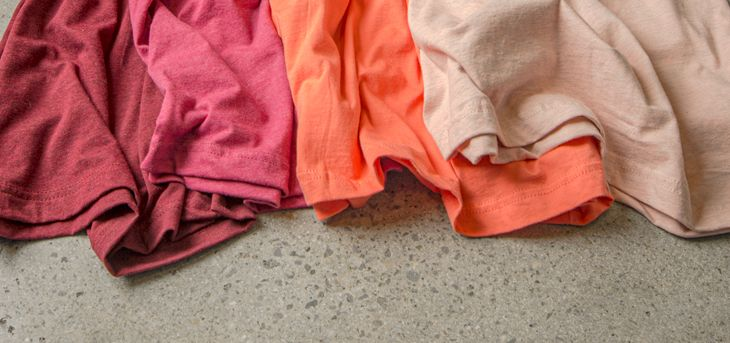 A detail image of various t-shirt colors that mimic the strawberries and cream color scheme.