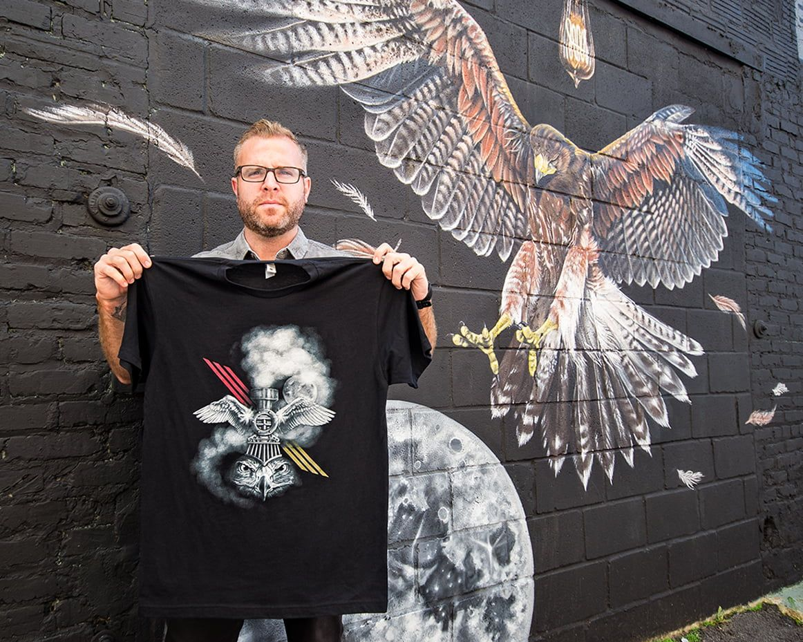 Artist Thomas Turner holding up his t-shirt standing in front of his mural painted for the OuterSpace project.
