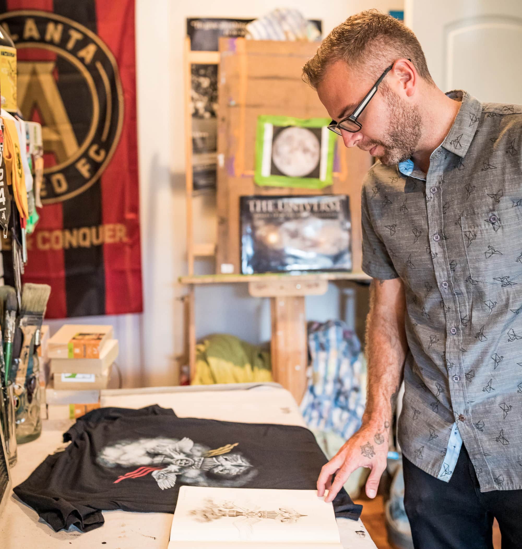 Artist Thomas Turner in his studio looking down at his sketch book and printed t-shirt.