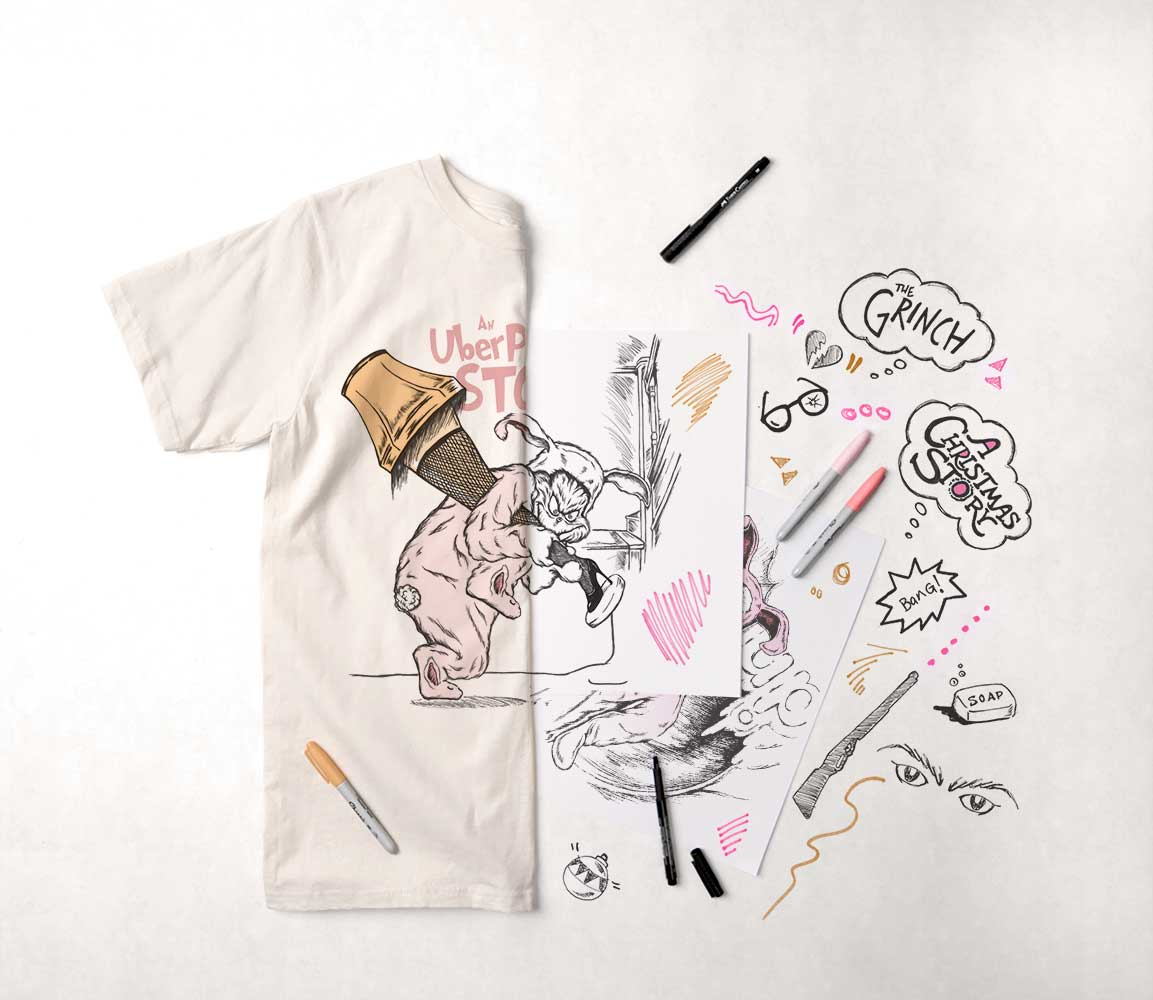 A display of drawing and design materials with the resulting printed t-shirt.