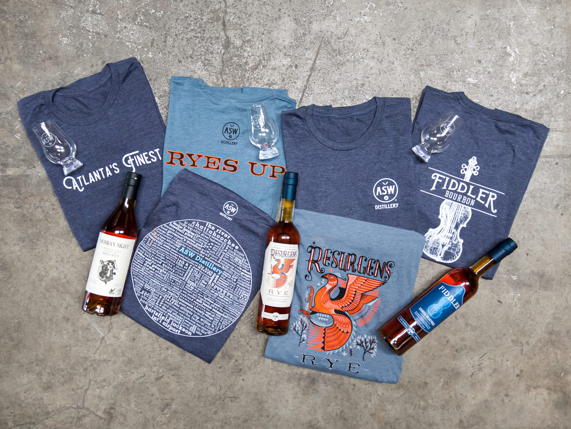 A topdown photo showing a variety of folded custom t-shirts for a distillery.