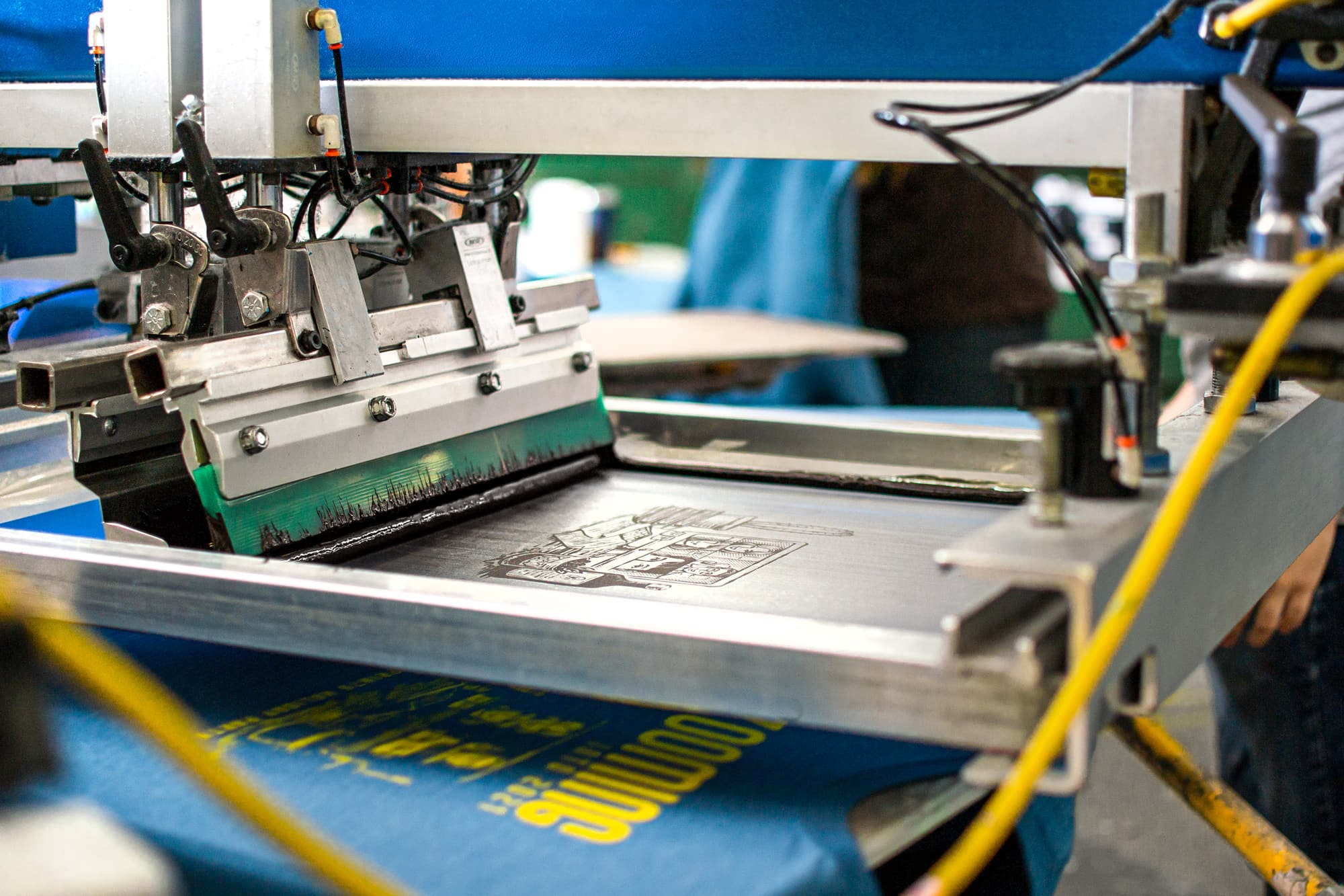 Image from the UberPrints warehouse showing a design being screen printed onto a shirt.